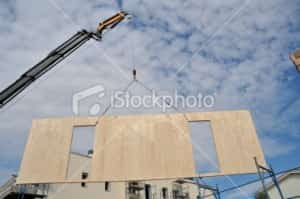 Crane lifting wall panel - stock photo