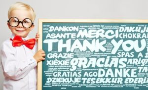 Boy in round glasses holding thank you sign